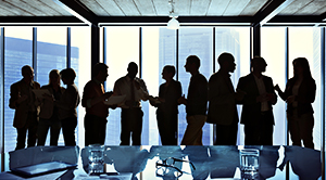 A group of business people having discussions in front of a large office windo.